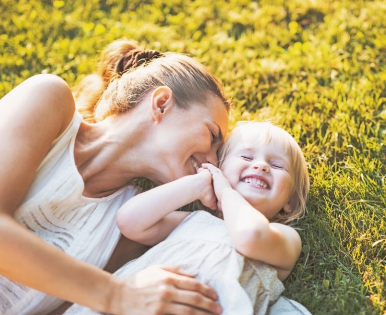 woman and child laying on grass laughing